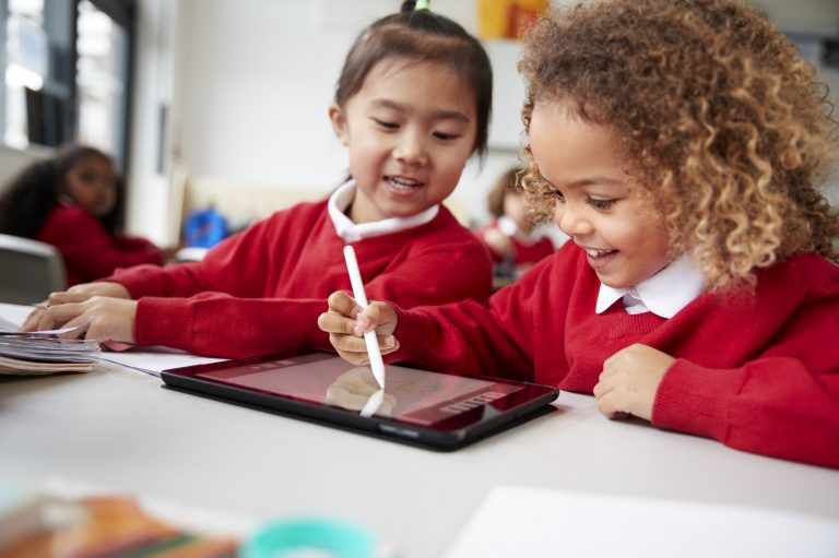 Close up of two kindergarten schoolgirls using a tablet computer and stylus, smiling