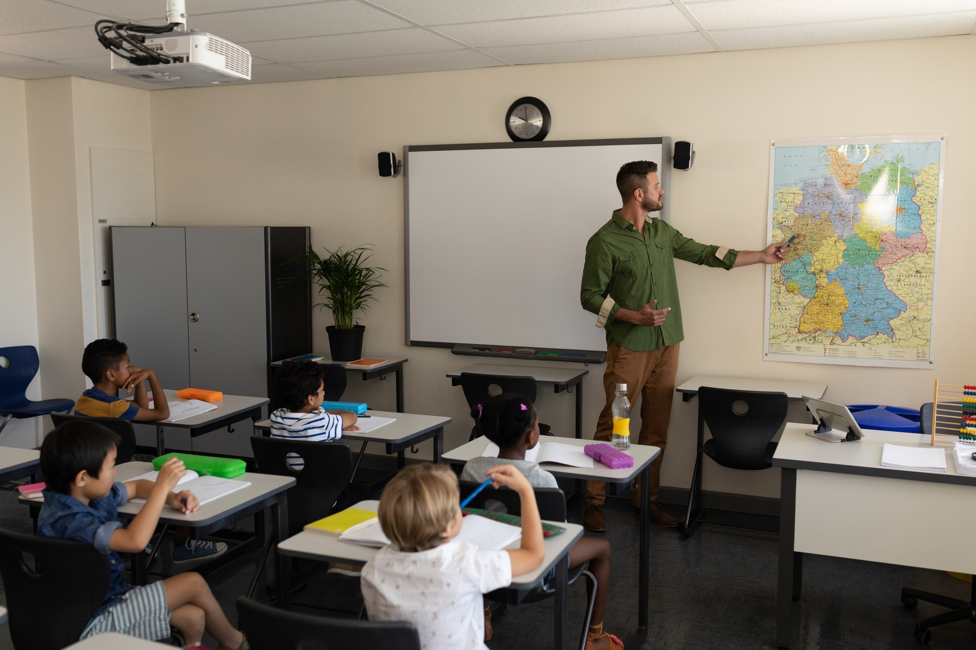 Teacher pointing at a map in classroom of elementary school